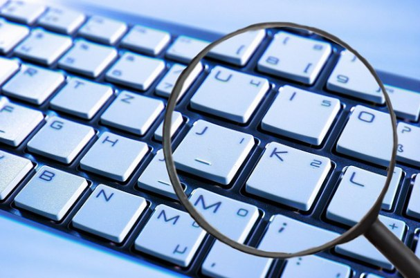 Cyber attack image of keyboard with magnifying glass over it