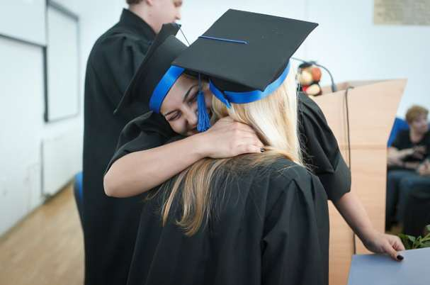 Recent College Grads With Two Graduate Women Hugging After Ceremony