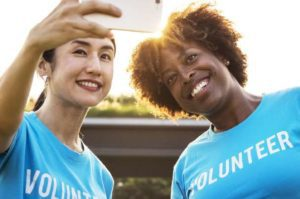 Charitable giving image with two women wearing volunteer shirts and taking a selfie