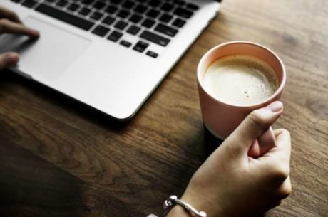 Using Tech to Stay on Track With Computer and Woman Holding Cup of Coffee