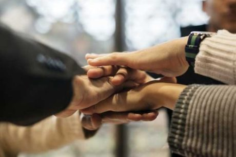 Plan your charitable giving image with people putting hands together in the middle of the group.