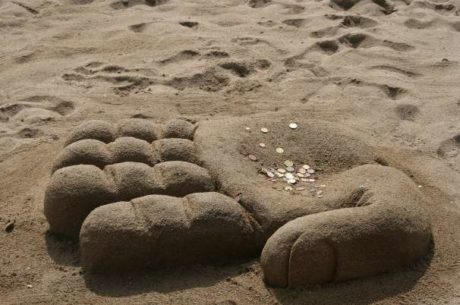 Bonus Incentive Plan Image Shows Hand Built of Sand on Beach with Coins in it