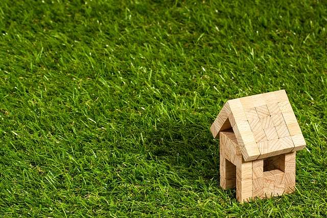 Inherit a home image shows a toy block wood home on grass