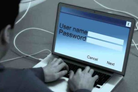 Password Manager Image of Man Typing User Name and Password on Laptop