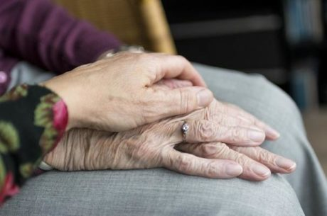 Financial exploitation picture of elderly woman with younger woman holding her hand