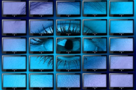 Credit Monitoring May Not Be Enough depicts woman's eye across 25 screens set in rows