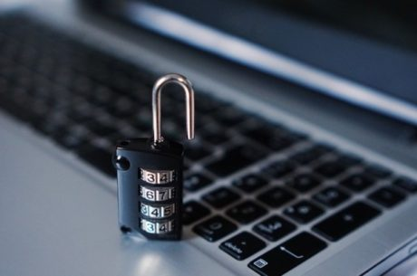 Browser security shows lock standing on a laptop keyboard