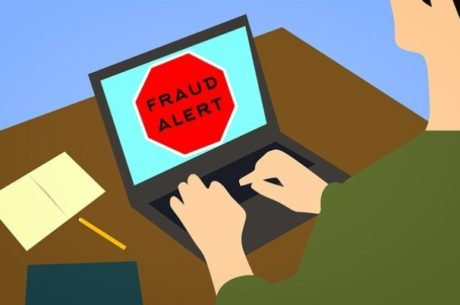 Avoiding holiday cyberscams depicts person typing on laptop that says fraud alert