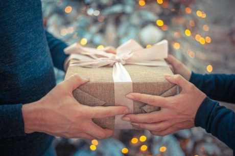 Charitable gifting image depicts a man and woman holding a present.