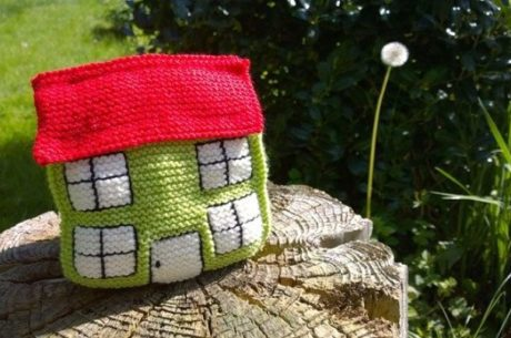 Reverse mortgage photo depicts a knitted house sitting on a tree stump.