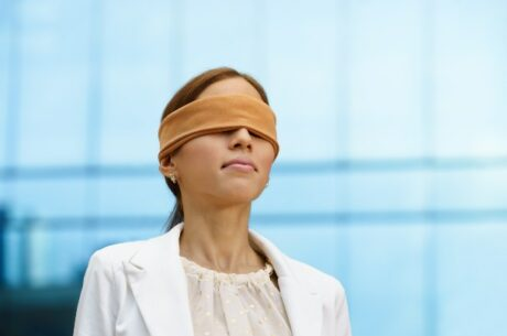 Using a blind trust to sell restricted stock depicts a blindfolded business woman