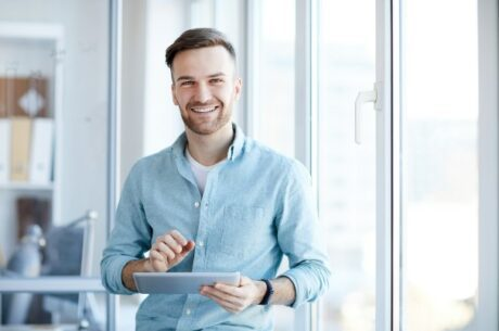 Effects of compound interest depicts young man holding a tablet