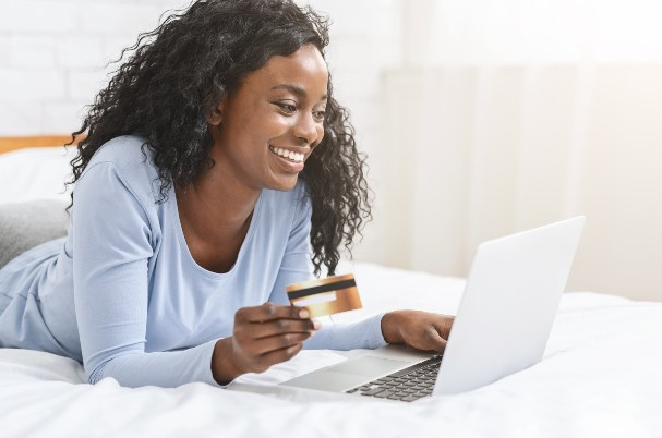 Woman on Laptop Holding a Credit Card