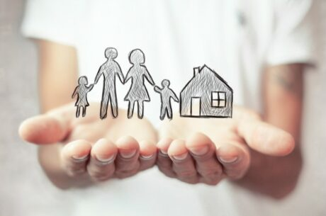 To Buy or Not to Buy . . . When Do You Need Life Insurance? Image shows hands protecting family and house.