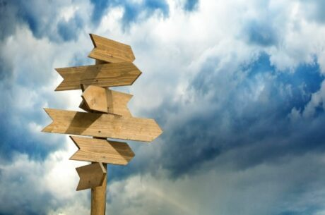 Social Security Timing Strategies - an Insider's Guide shows image of wooden signposts against the sky